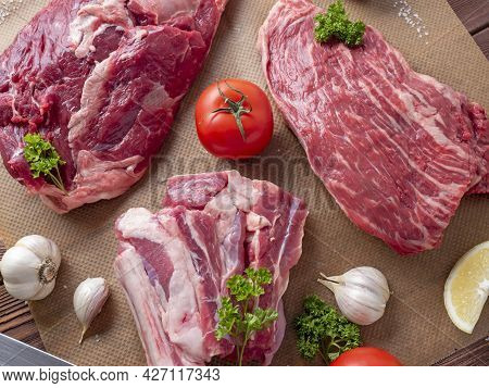 Several Pieces Of Raw Marbled Black Angus Beef Lie On Parchment Surrounded By Greenery And Vegetable