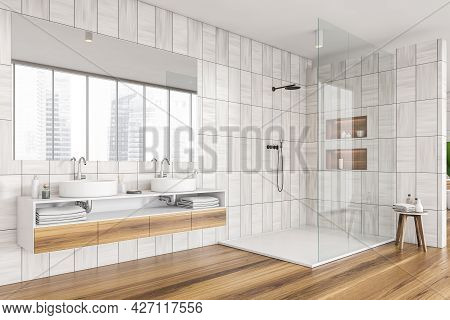 Corner Of Shower Room With Grey Beige Tiling Walls, Mirror, Two Basins With Shelf Beneath. Wooden Dr