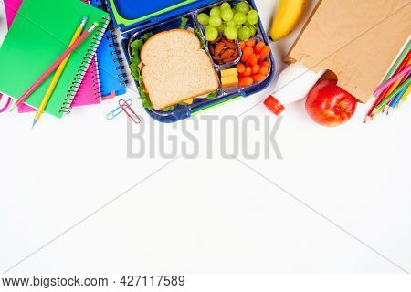 Healthy School Lunch With School Supplies. Above View Top Border On A White Background. Back To Scho