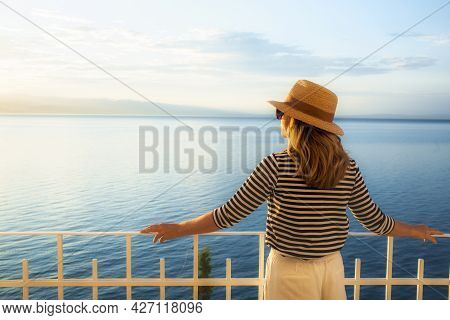 Shot Of Mature Woman Wearing Straw Hat And Sunglasses While Standing On Balcony And Looking At Sea V