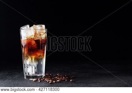 Cold Drink With Espresso And Tonic In Glass On Black Background