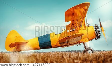 Sideview Of An Historical Biplane On A Meadow