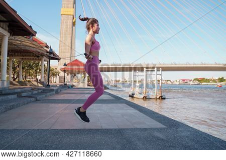 Fit Asian Female Practicing Cardio Workout With A Skipping Rope For Weight Loss. Young Woman Standin