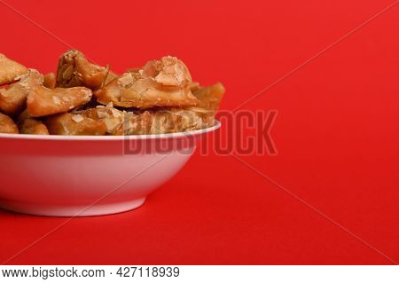 Isolated Studio Shot On Red Background Of Cropped Plate With Delicious Arabian Moroccan Dessert For