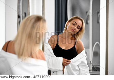 A Charming Gorgeous Woman Looking In The Mirror, Satisfied With Her Young, Perfect And Aesthetic Bod
