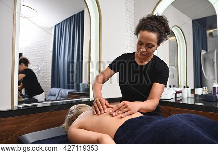 Female Masseur Performing Back Massage To Woman Relaxing On Massage Couch While Visiting Clinic In S