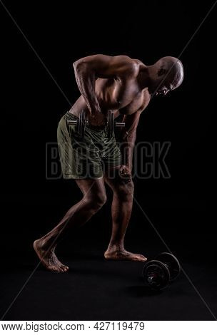 Side View Of A Muscular Man Standing Leaning Forward Doing Triceps Exercise