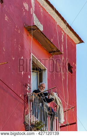 Naples, Italy - January 21, 2017: A Gentleman Standing On The Balcony In The Historical District Of