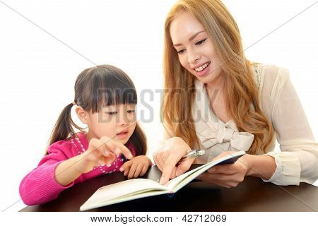 Little girl studying in English with teacher