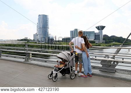 Moscow, Russia - July 2021: Couple With Baby Pram Standing On The Pavshinsky Pedestrian Bridge On Ba
