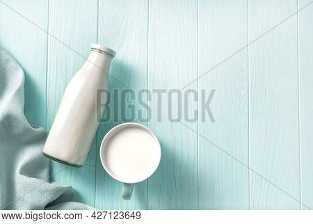 A Bottle Of Milk And Mug Of Milk On A Wooden Table. Top View Of Milk On A Blue Background
