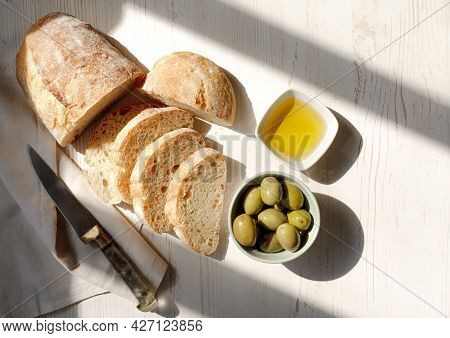 Sliced Organic Bread Ciabatta With Vintage Linen Napkin And Bowl Of Olive Oil, Olives On White Woode