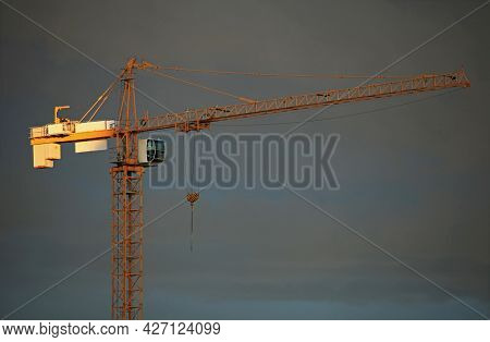 Single Construction Crane On The Gray Sky Background In The Rays Of Yellow Evening Sun. Building Con