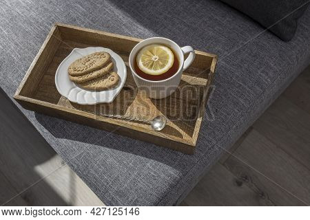 A White Cup Of Tea With Lemon, A Long Cupronickel Spoon With A Twisted Handle And A Saucer With Thre