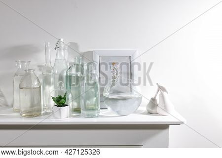 A Set Of Water Bottles Of Different Shapes With A Photo Frame And A Pot With Artificial Succulent Is