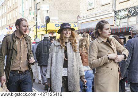London, Uk - November 2019, Young Man And Woman Walking Through The Crowd On Brick Lane