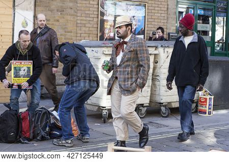 London, Uk - November 2019, A Fashionable Man In A Cap And Plaid Jacket Walks Past A Protesting Man