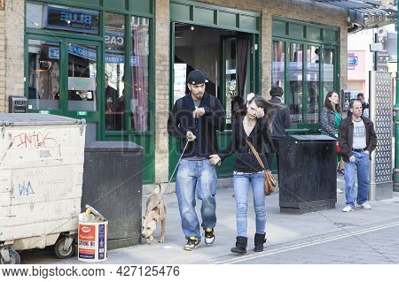 London, Uk - November 2019, A Man In A Cap And A Woman With Long Hair With A Fighting Dog At A Sunda