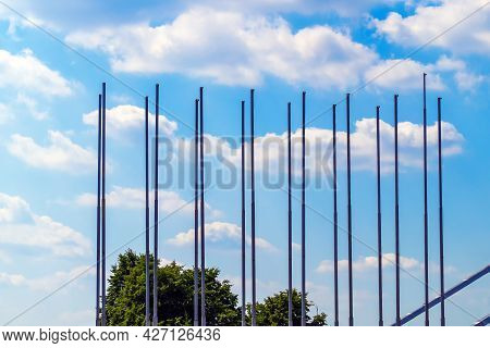 A Lot Of Empty Flagpoles Against The Sky With Clouds. Trees. Flags Removed.