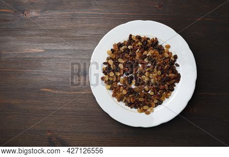 Raisins In Plate On Wood Table Background. Flat Lay.