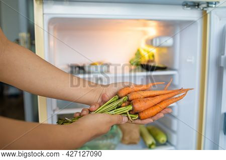 Woman\'s Hand Holding Bunch Of Carrots In Front Of The Refrigerator In Kitchen.