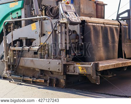 Close-up Back View Of An Road Paver In The Process Of Paving Asphalt.