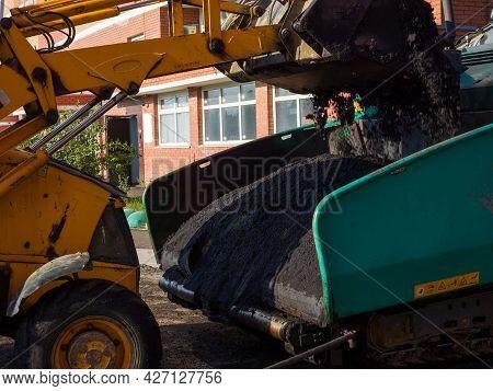 A Close-up Of An Excavator Bucket Unloading Fresh Hot Asphalt Into The Receiving Hopper Of An Asphal