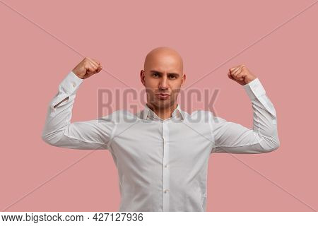 Strong Bald Man With Bristle Posing Raises Hands And Shows Muscles, His Strength And Power, Feels Pr