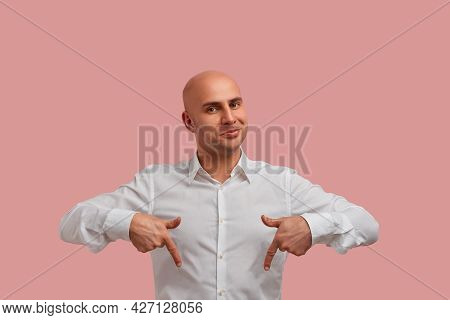This Place Os Perfect. Horizontal Photo Of Joyful Bald Man With Mysterious Smile, Points Down And Sh