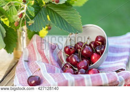 An Overturned Cup With Ripe Cherries On The Table. Decor With A Fabric Red Towel And A Bouquet Of St