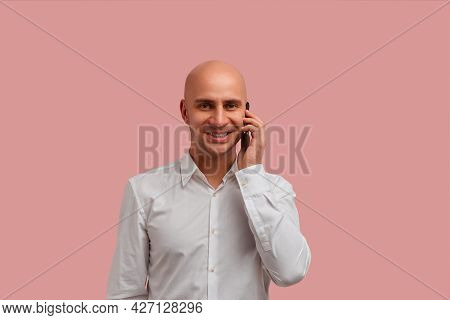 Communication At A Distance. Smiling Bald Man With Bristle Holds Smartphone Near Ear, Looks Happy. T