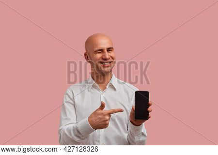 Horizontal Photoshot Of Funny Bald Man With Bristle In White Shirt, Winks And Points To Blank Of Sma
