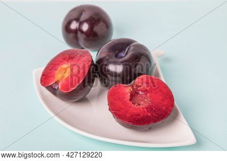 On A White Saucer Is A Large Plum, Cut In Half, And Next To It Is A Whole Plum. The Pulp Of Red Berr