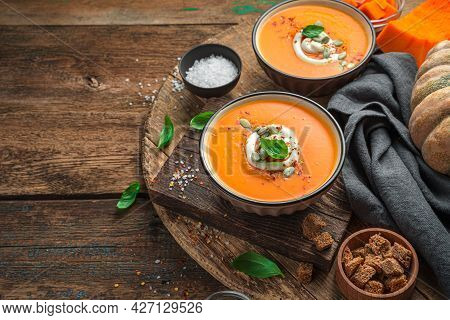 Two Servings Of Pumpkin Cream Soup On A Wooden Background With Ingredients And Spices. Side View, Sp
