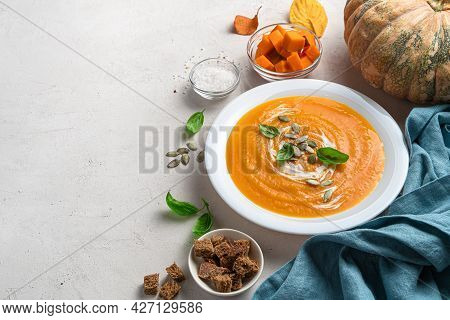 Pumpkin Cream Soup With Pumpkin Seeds And Basil On A Gray Background. Side View, Space For Copying.