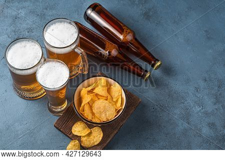 Beer Mugs, Chips And Beer Bottles On A Dark Blue Background. Horizontal View, Space For Copying. Okt