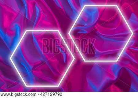 Light Frames On Pleated Santine Fabric In Neon Light. Creative Abstract Background For Yor Text