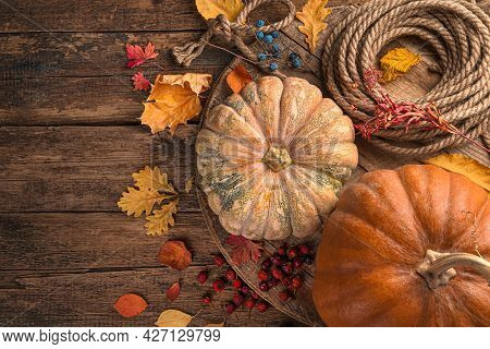 Pumpkins And Yellow Leaves On A Wooden Brown Background. Background For Autumn Holidays: Thanksgivin