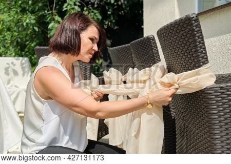 Woman Decorating Outdoor Chairs For Party, Ceremony