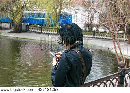 Dnepropetrovsk, Ukraine - 04.06.2021: A Girl With A Mobile Phone In Her Hands In A Park Near The Pon