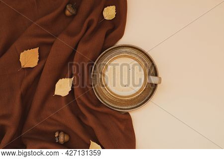 Atmospheric Autumn Composition. Fall Background With Mug Of Coffee, Deep Brown Cashmere Scarf And Le