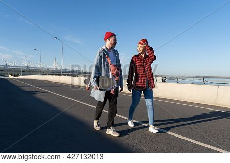 Trendy Couple Of Millennial Male And Female Walk Together On Bridge After Longboard Skating. Hipster