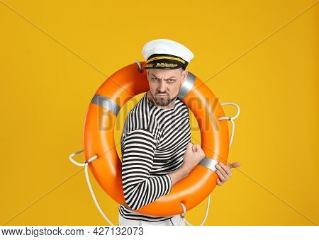 Serious Sailor With Orange Ring Buoy Showing Biceps On Yellow Background