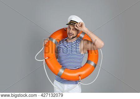 Sailor With Orange Ring Buoy On Grey Background