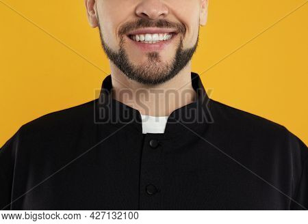 Priest Wearing Cassock With Clerical Collar On Yellow Background, Closeup