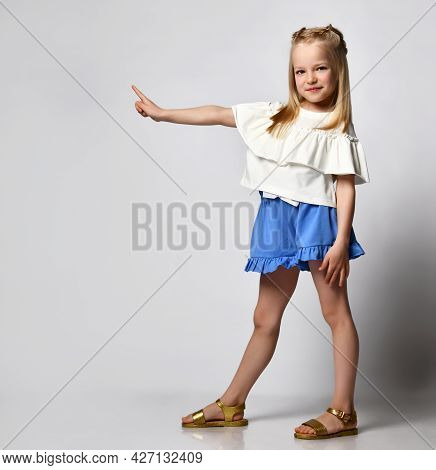 Little Cute Girl Shows A Finger To The Side While Standing On A White Background. Studio Portrait Of