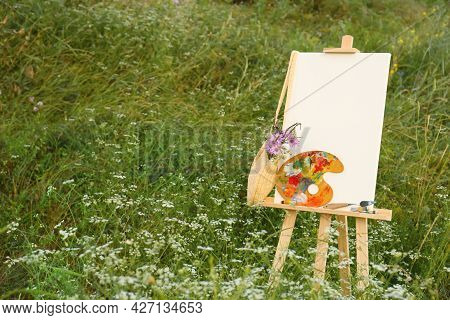 Wooden Easel With Blank Canvas, Painting Equipment And Flowers In Meadow. Space For Text