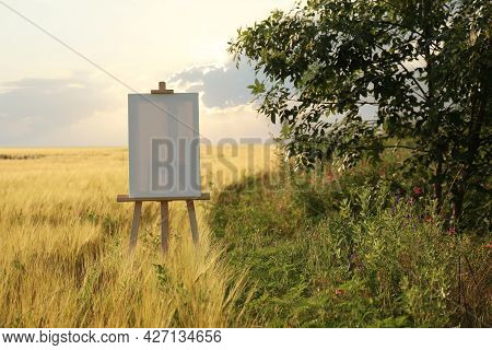 Wooden Easel With Blank Canvas In Field. Space For Text