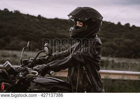 Portrait Of Confident Motorcyclist Woman In Motorcycle Helmet. Young Driver Biker Looking Away Outdo