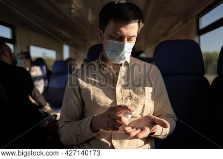 Travel Safely On Public Transport. Young Man With Face Mask Using Wash Hand Sanitizer Gel Dispenser.